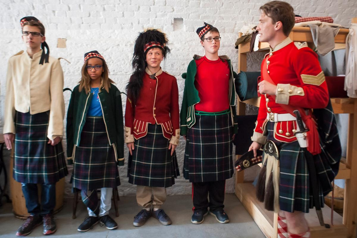 Students in Scottish garb with a tour guide