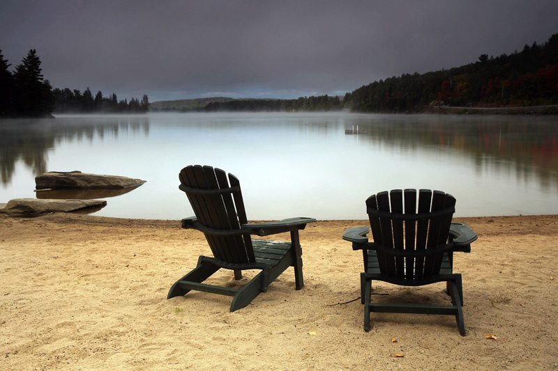 Muskoka Chairs on a beach by a lake